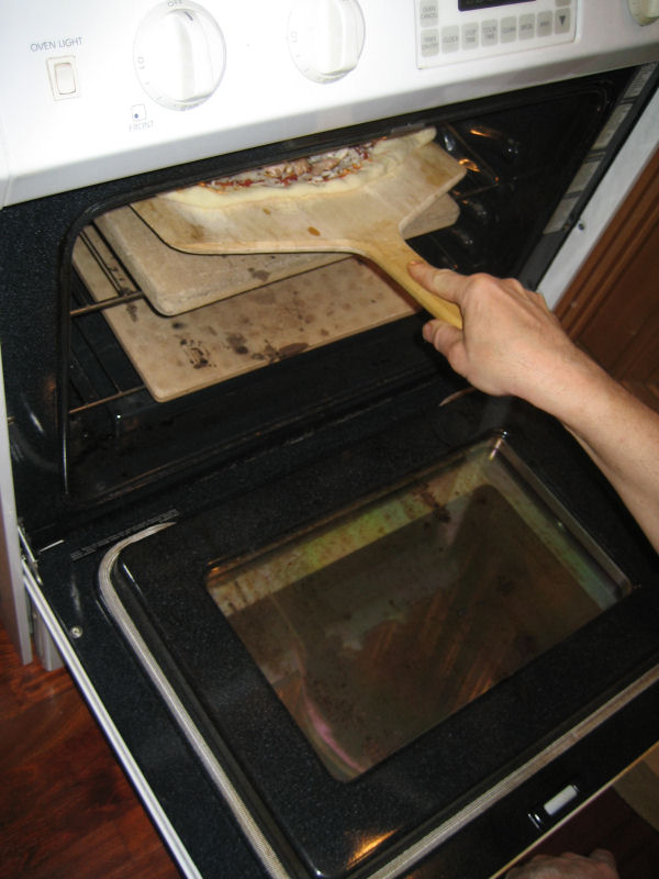 sliding pizza off wood peel into oven